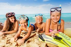 Group of kids lay on the beach in snorkeling masks stock photography