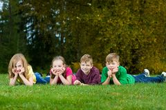 A group of kids laying down in the grass Stock Photos
