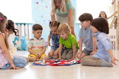 Group of kids learning time with clock toy. In kindergarten royalty free stock photography