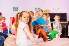 Group of kids listen to teacher reading book Stock Image