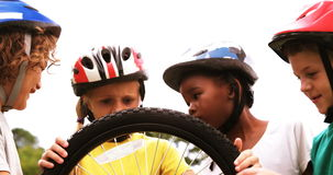 Group of kids looking at bicycle wheel stock footage