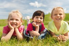 Group of kids lying on blanket or cover outdoors Royalty Free Stock Image