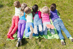 Group of kids lying on blanket or cover outdoors Royalty Free Stock Images