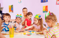 Group of kids make paper crafts in kindergarten Stock Photos