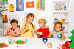 Group of kids paint New Year balls for Xmas tree Royalty Free Stock Photo