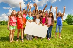 Group of kids with placecard. Many boys and girls holding blank banner showing blank placard board to write it on your own text, standing on the grass field on Stock Images
