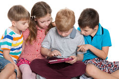 Group of kids plaing with a gadget Stock Photo