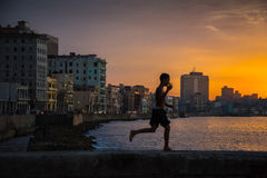 Group of kids play and jump from Malecon wall into Atlantic in H Stock Photography
