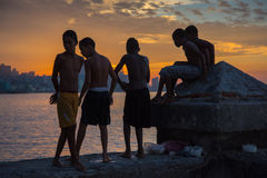 Group of kids play and jump from Malecon wall into Atlantic in H Royalty Free Stock Photo