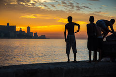 Group of kids play and jump from Malecon wall into Atlantic in H Royalty Free Stock Photos