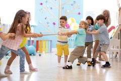 Group of kids play and pull rope together in daycare. Group of preschool kids play and pull rope together in daycare stock images