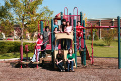 Group of kids on playground. Diverse group of multi-ethnic kids on swingset Royalty Free Stock Photography