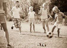 Group of kids playing football together on green lawn in park Stock Image