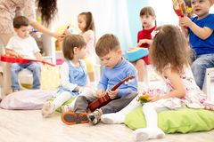 Group of kids playing musical toys. Early musical education in kindergarten royalty free stock image