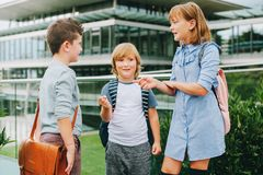 Group of three funny kids wearing backpacks walking back to school Royalty Free Stock Images