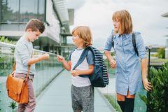 Group of three funny kids wearing backpacks walking back to school Royalty Free Stock Image