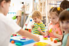 Group of kids playing together in the classroom in kindergarten or preschool. Group of children playing together in the classroom in kindergarten or preschool stock images