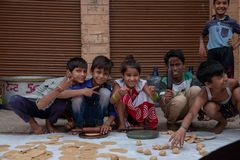 A group of kids pose for a photo while rolling roti. stock images