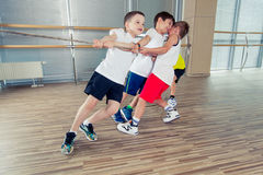 Group of kids pulling a rope in fitness room.  Royalty Free Stock Image