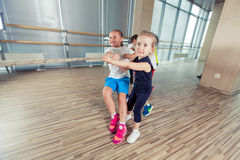 Group of kids pulling a rope in fitness room.  Stock Image