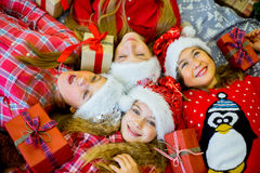 Group of kids in red hat with Christmas gifts Royalty Free Stock Images