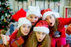 Group of kids in red hat with Christmas gifts Stock Images