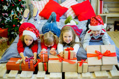 Group of kids in red hat with Christmas gifts Stock Photography