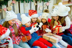 Group of kids in red hat with Christmas gifts Royalty Free Stock Photos
