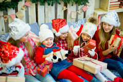 Group of kids in red hat with Christmas gifts Royalty Free Stock Photography