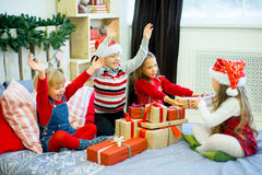 Group of kids in red hat with Christmas gifts Royalty Free Stock Image
