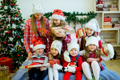 Group of kids in red hat with Christmas gifts. Group of kids in red hat sitting on the bed next to the Christmas tree holding gifts and smiling Stock Photography