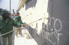A group of kids repainting the side of a building defaced by graffiti Royalty Free Stock Photos