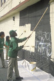 A group of kids repainting the side of a building defaced by graffiti Stock Image