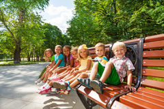 Group or kids rest on bench in park. Group of beautiful and cute kids, boy and girls, Caucasian and black sitting happy on the bench in sunny park Royalty Free Stock Image