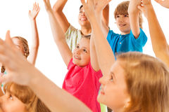 Group of kids rise hand with focus on little girl Stock Photo