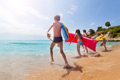 Group of kids run into the sea on sunny beach Stock Photo