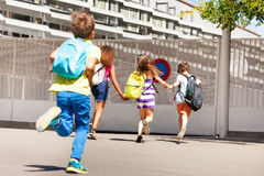 Group of kids run to school one after another royalty free stock photos