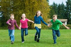 A group of kids running in grass Royalty Free Stock Photo