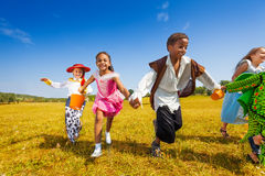 Group of kids running in Halloween costumes Stock Photo