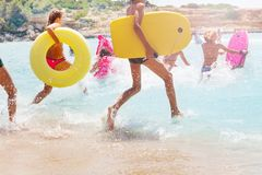 Group of kids running into sea to swim. Group of many kids running into the sea water with equipment board inflated swim rings making splashes stock photos