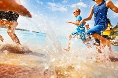 Kids having fun run make splashes in shallow water. Group of kids running in shallow sea water making splashes in summer sunny day Royalty Free Stock Images
