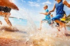 Kids having fun run make splashes in shallow water Royalty Free Stock Images