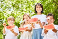 Group of kids serving fresh watermelons stock photo