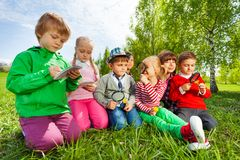 Group of kids sit in the field with magnifier Stock Images