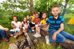 Group of kids sit near bonfire with marshmallow royalty free stock photo