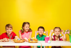 Group of kids sit at the table with Easter eggs. And tulips on the yellow background stock photos