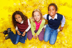 Group of kids sitting on autumn leaves Royalty Free Stock Image