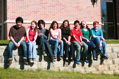 Group of kids sitting on wall stock photo