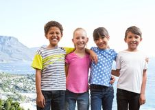 Group of kids smiling against blurry coastline Stock Image