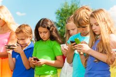 Group of kids sms. Group of busy kids looking at their phones texting sms and playing staying outside Stock Photo